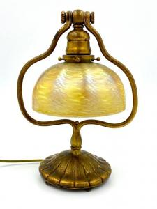 Tiffany Studios desk lamp with a gilt bronze harp form base with ribbed circular foot and a (cracked) Tiffany favrile glass damascened shade in gold ($4,612).