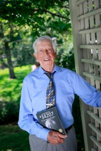 Joe Rubinstein holding a copy of the book about his life: Auschwitz #34207 The Joe Rubinstein Story (photo by Crystal Merrill 2019)