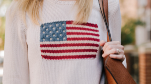 Women wearing a knitted sweater with an American flag on it.
