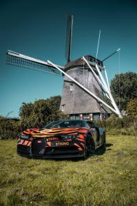 Bugatti Chiron wrapped in tiger stripes, emblazoned with Tiger King Coin and Joe Exotic decals, parked in front of a windmill in the Netherlands