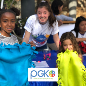 Two children hold up hand-made blankets, next to a volunteer in a Project Giving Kids t-shirt, at a Create the Change volunteer event.