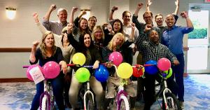 A team poses with bikes they built together in TeamBonding's Charitable Bike Build activity.