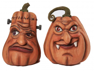 Two pumpkin table pieces. One resembles a vampire and the other, Frankenstein's monster.