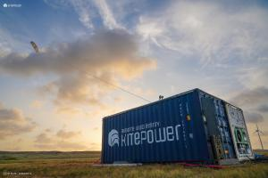 Kitepower containerised wind energy system and battery in a field on Aruba