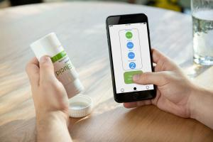 Person using the PillConnect Bottle and smartphone app