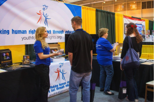 Erica Rodgers, National Director for Youth for Human Rights International showing the educational booklet to an educator at a teachers' convention