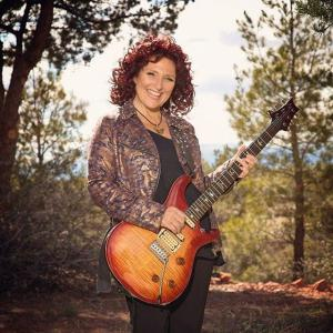 Valerie with her guitar in the Arizona forest