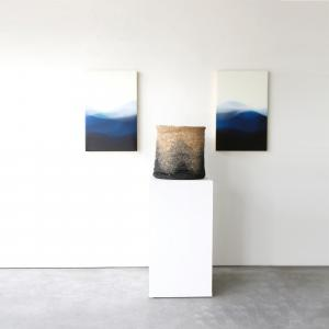 """Marina Dunbar's Landless measures 40"""" x 30"""" and sits next to a hand woven basket in blue and black ombre"""