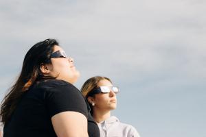 Mujeres viendo con seguridad el eclipse solar
