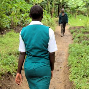 girl in school uniform walks away from camera along a rural path through a jungle, coming towards her is a man, whose image is out of focus