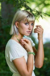 Model wearing green pieces of jewelry.