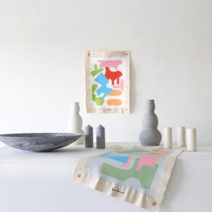 """This is an image of work by The Holey Kids small canvases sized 30"""" x 20"""" with colorful shapes, sitting by ceramic containers in greys and whites"""