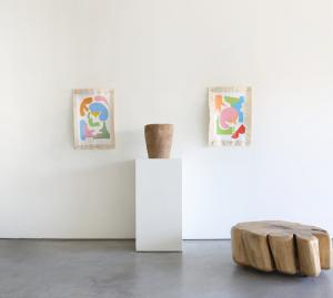 This is an image of 2 works by The Holey Kids alongside 2 wooden sculptural pieces. The Holey Kids work is brightly colored shapes on grommeted canvas