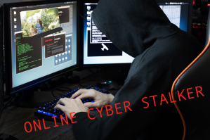 Stalker sitting in a dark room with two computer screens stalking a woman in business.