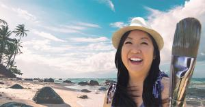 Photo of Hawaii artist Jan Tetsutani looks happy wearing a hat and holding her paintbrush at a sunny beach in Hawaii